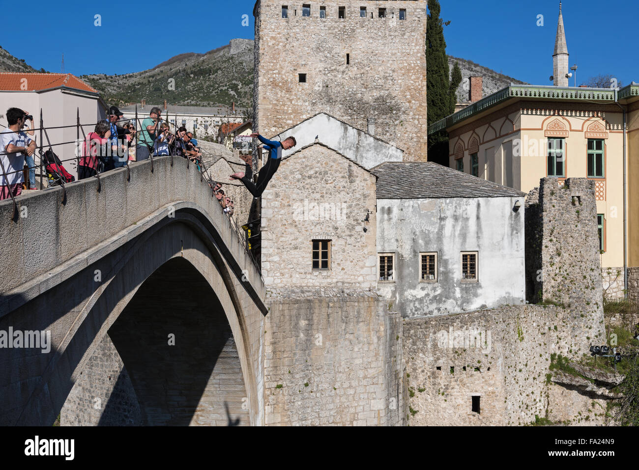 A young man dives from the Old Bridge to the river on April 15, 2015 in Mostar, Bosnia and Herzegovina. - Stock Image