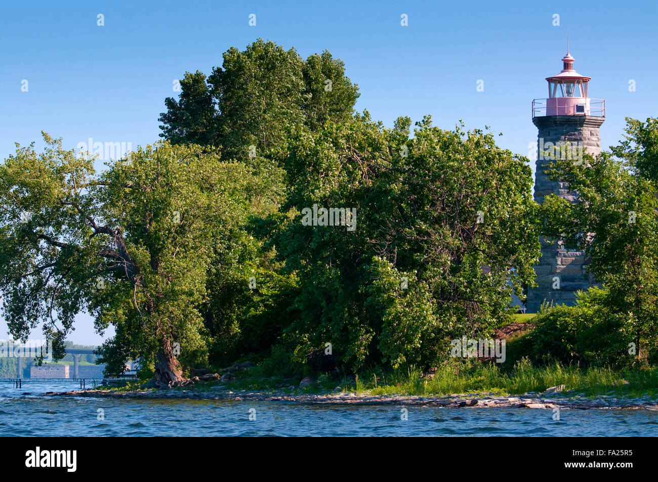 Stone tower of Windmill Point lighthouse surrounded by green trees on the shoreline of Lake Champlain, in Vermont. - Stock Image