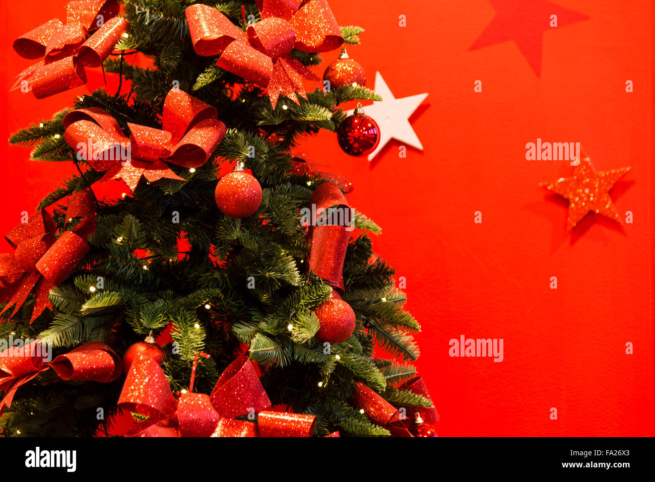 Christmas tree decorated with red baubles & ribbons, UK. - Stock Image