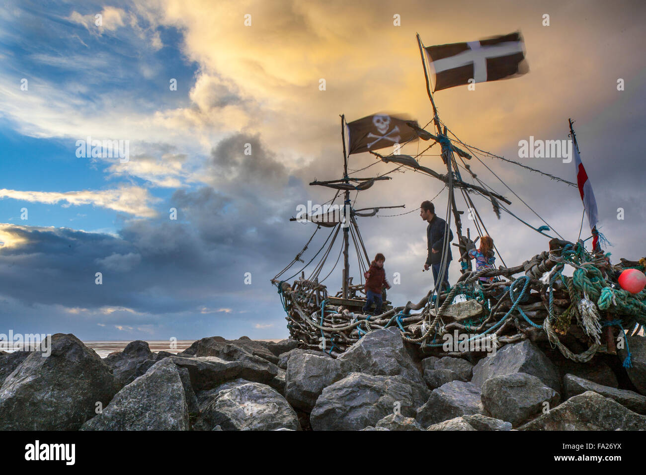 """Hoylake, Wirral, 20th December, 2015.   UK Weather.  Storm skies over the Driftwood Boat, a children art project.  The 'Grace Darling' a sculpture on Hoylake's shore. Hoylake's very own pirate ship named after Grace Darling who aged 22 rowed out in a storm with her father to help survivors of the SS Forfarshire, wrecked off the Farne Islands in 1838.  Since she was """"berthed"""" on the rocks by the new Hoylake Lifeboat station in Summer 2013, hundreds of children (and grown-ups) have clambered over Grace and enjoyed her close-up and from afar. Stock Photo"""