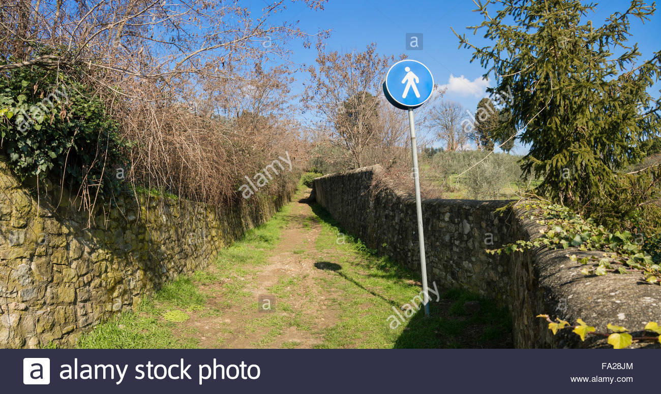 Panoramic view of a long narrow country path between stone walls with a city signpost reserving it to pedestrians - Stock Image