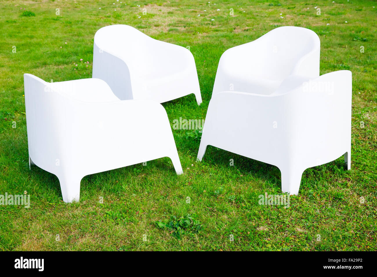 Four Modern White Plastic Chairs Stand On Fresh Green Grass Stock Photo Alamy