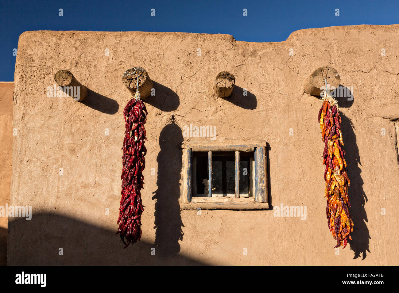 Dried chile pepper ristras hang on an adobe wall at the ancient ...