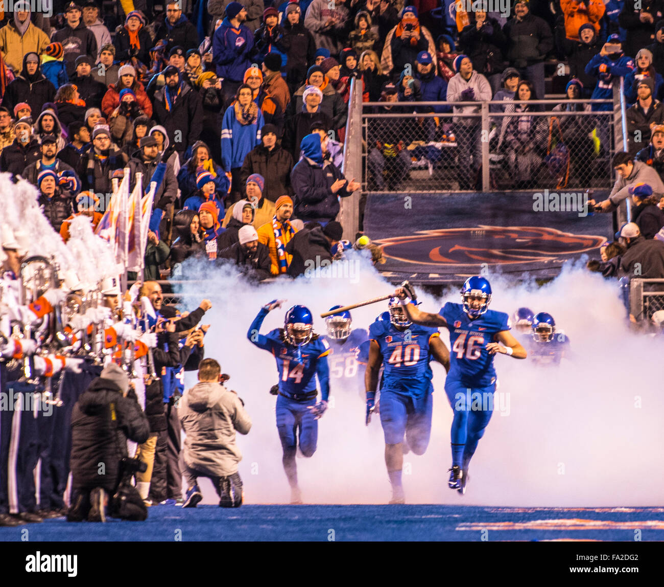 Football, Boise State football team entering Albertson's Stadium blue field through fog cloud before game time. - Stock Image