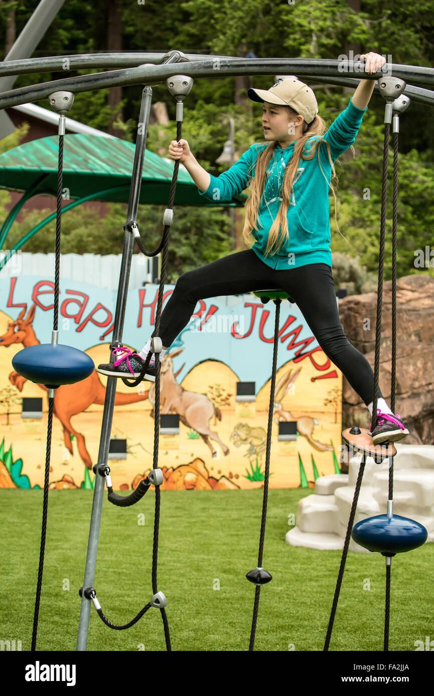 Nine year old girl climbing on playground equipment at the Woodland Park Zoo in Seattle, Washington, USA - Stock Image