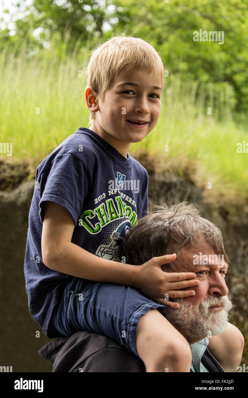 Seven year old boy getting a piggyback ride from his grandfather in Seattle, Washington, USA - Stock Image