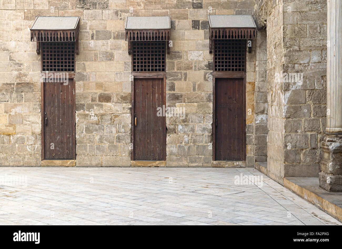 Three doors in a stone wall at the main courtyard in a historic mosque & Three doors in a stone wall at the main courtyard in a historic ...