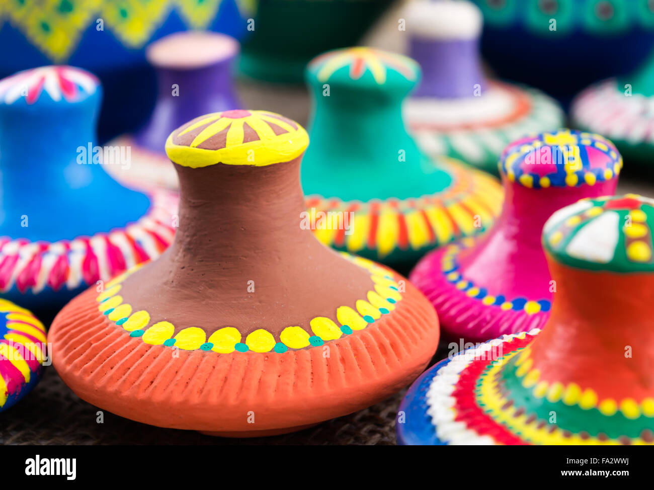 A group of painted  handmade pottery vessels top covers - Stock Image