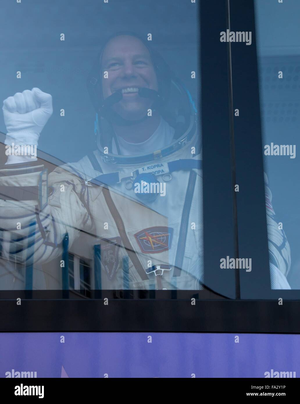 International Space Station Expedition 46 crew member American Tim Kopra waves from a bus as he depart Building - Stock Image