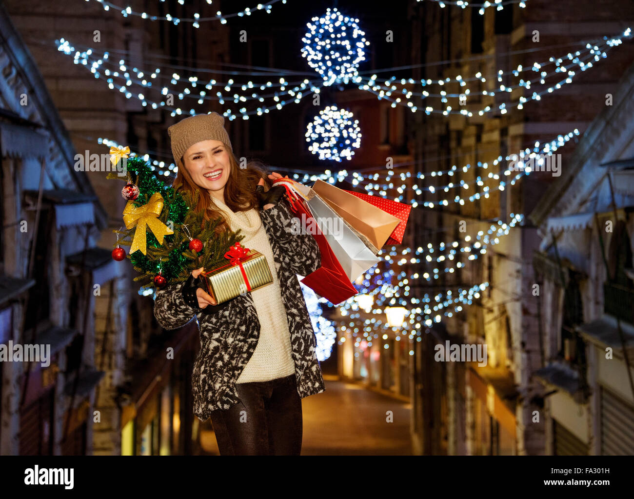 This Christmas is crushing on fashion forward shopping. Portrait of stylishly dressed smiling young woman holding - Stock Image