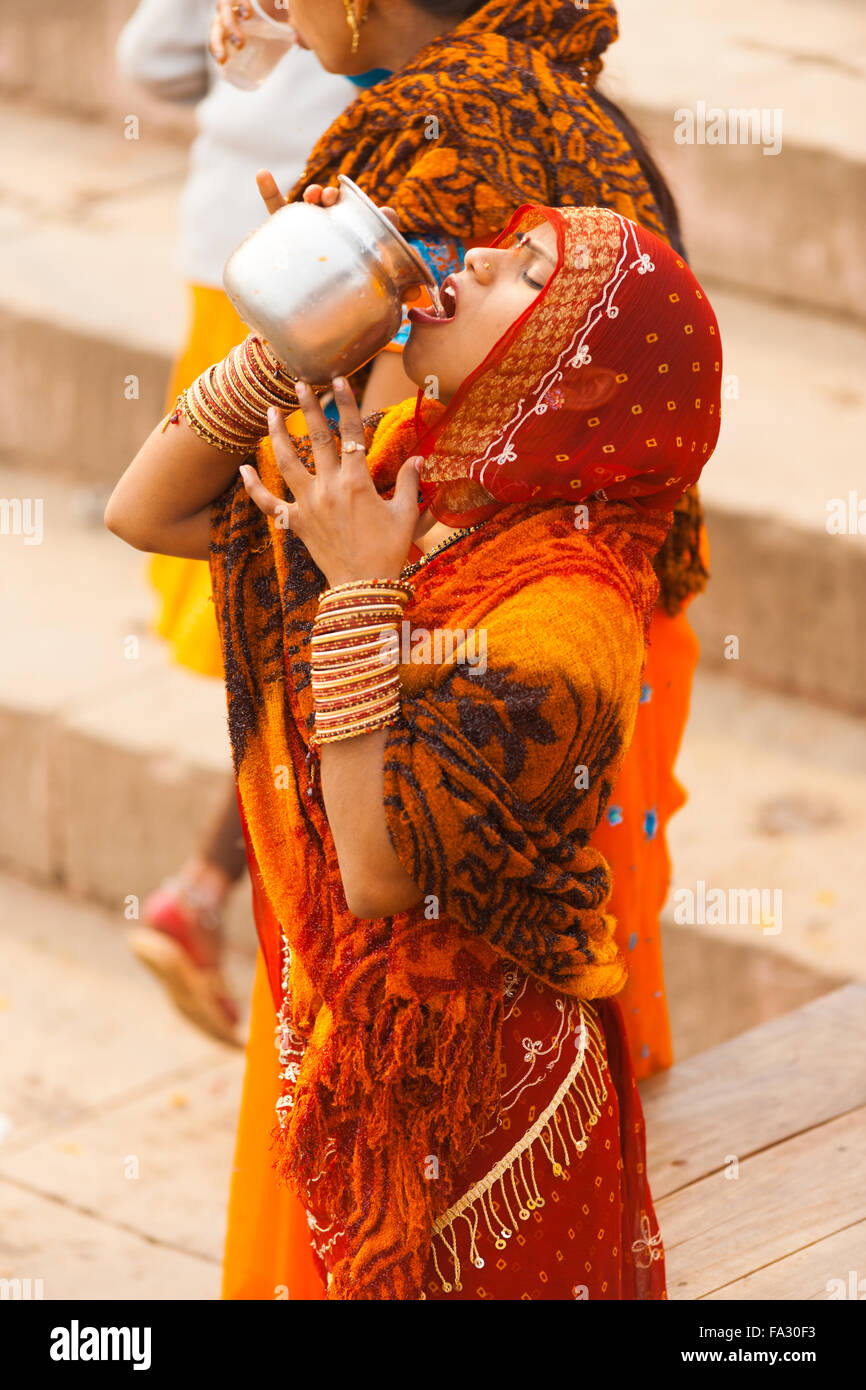 A young Indian woman in red saree pouring into mouth, drinking unhygienic Ganges river water from an urn following - Stock Image
