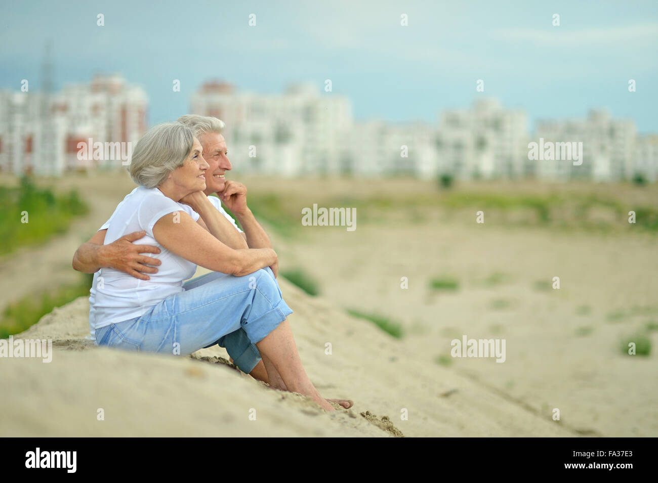 Elderly couple sitting on sand - Stock Image