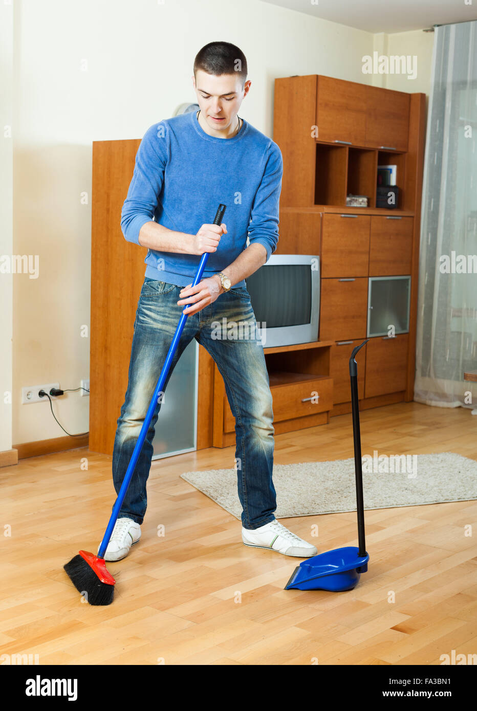 smiling man sweeping the floor in living room at home stock photo alamy https www alamy com stock photo smiling man sweeping the floor in living room at home 92273469 html