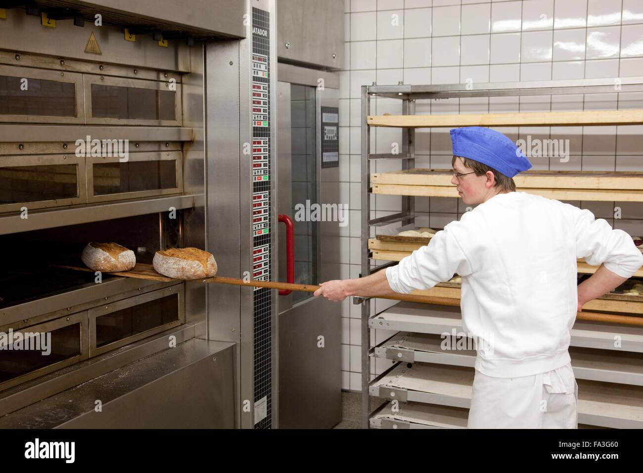 Baker apprentice baked bread. - Stock Image