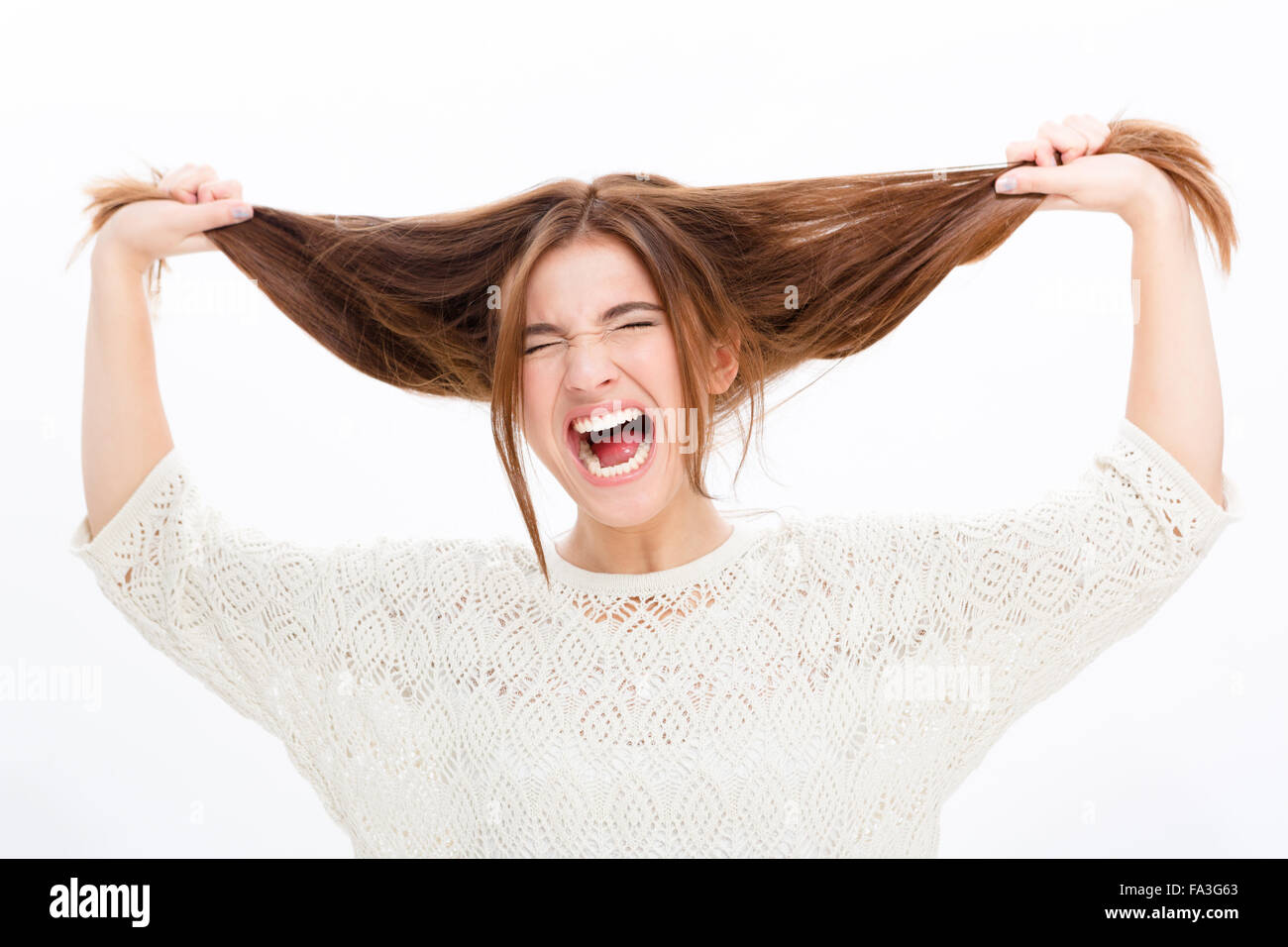 Desperate hysterical shouting young woman in black clothes over white background - Stock Image
