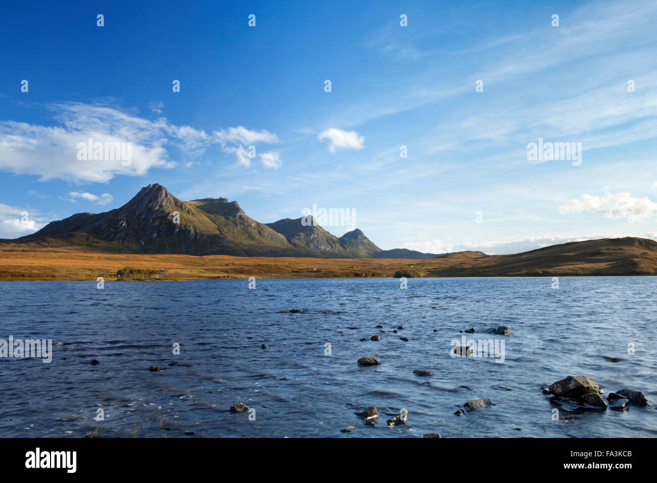The mountain range of Ben Loyal with the loch below, in late afternoon sunlight. - Stock Image