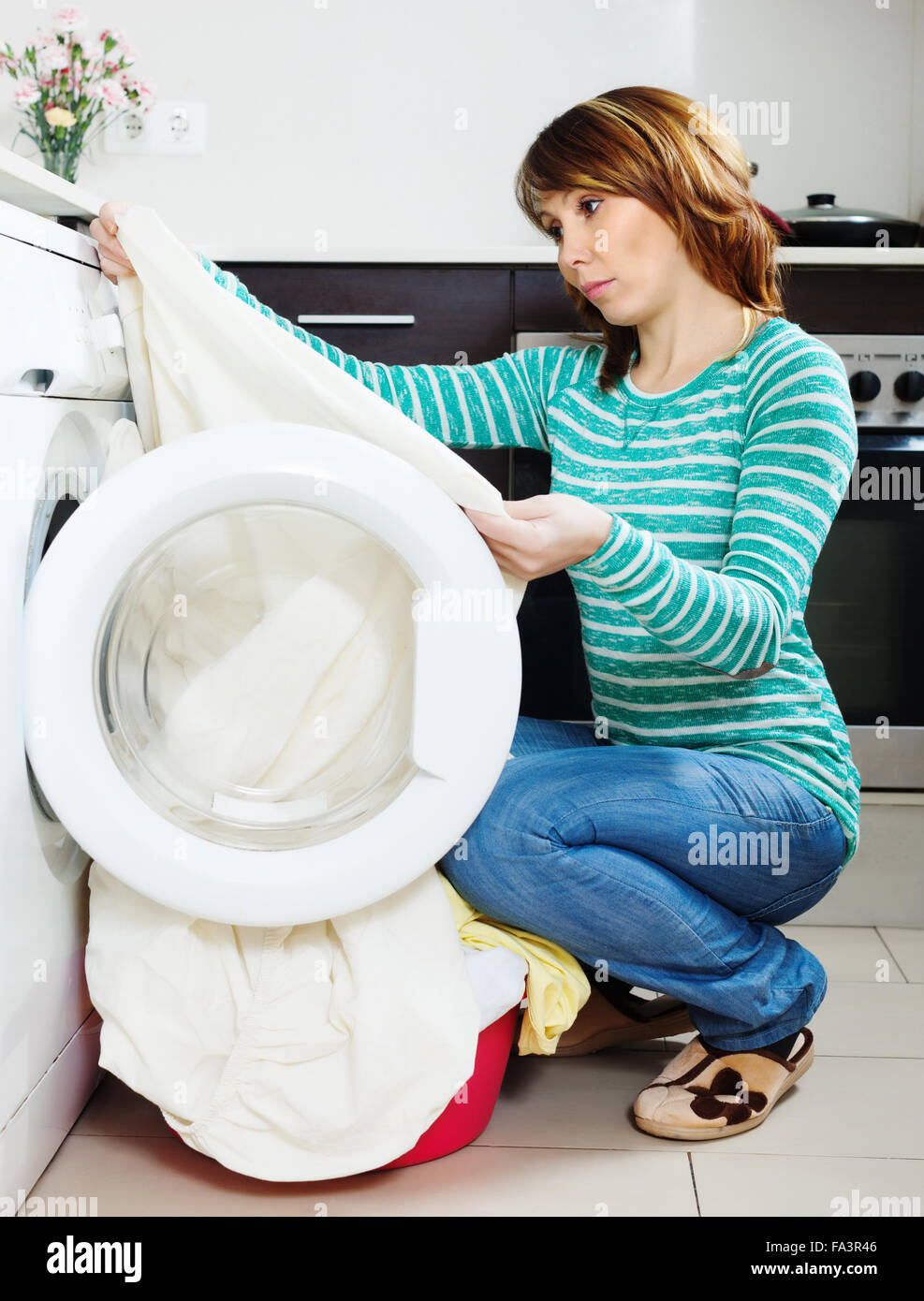 Unhappy woman doing laundry with washing machine at home kitchen ...