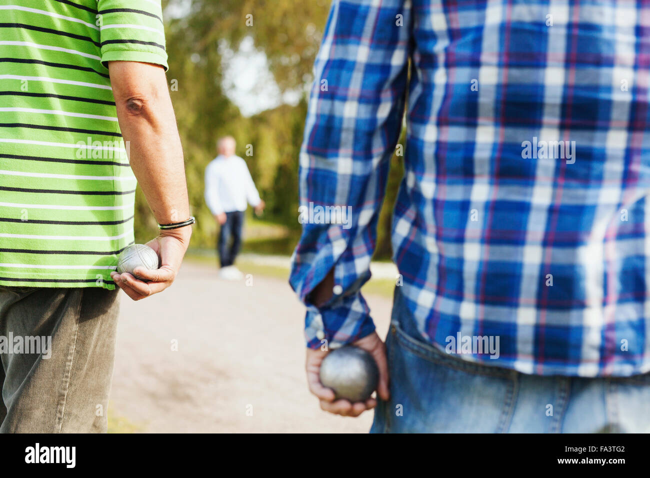 Rear view of men holding balls while playing boule on footpath at park - Stock Image