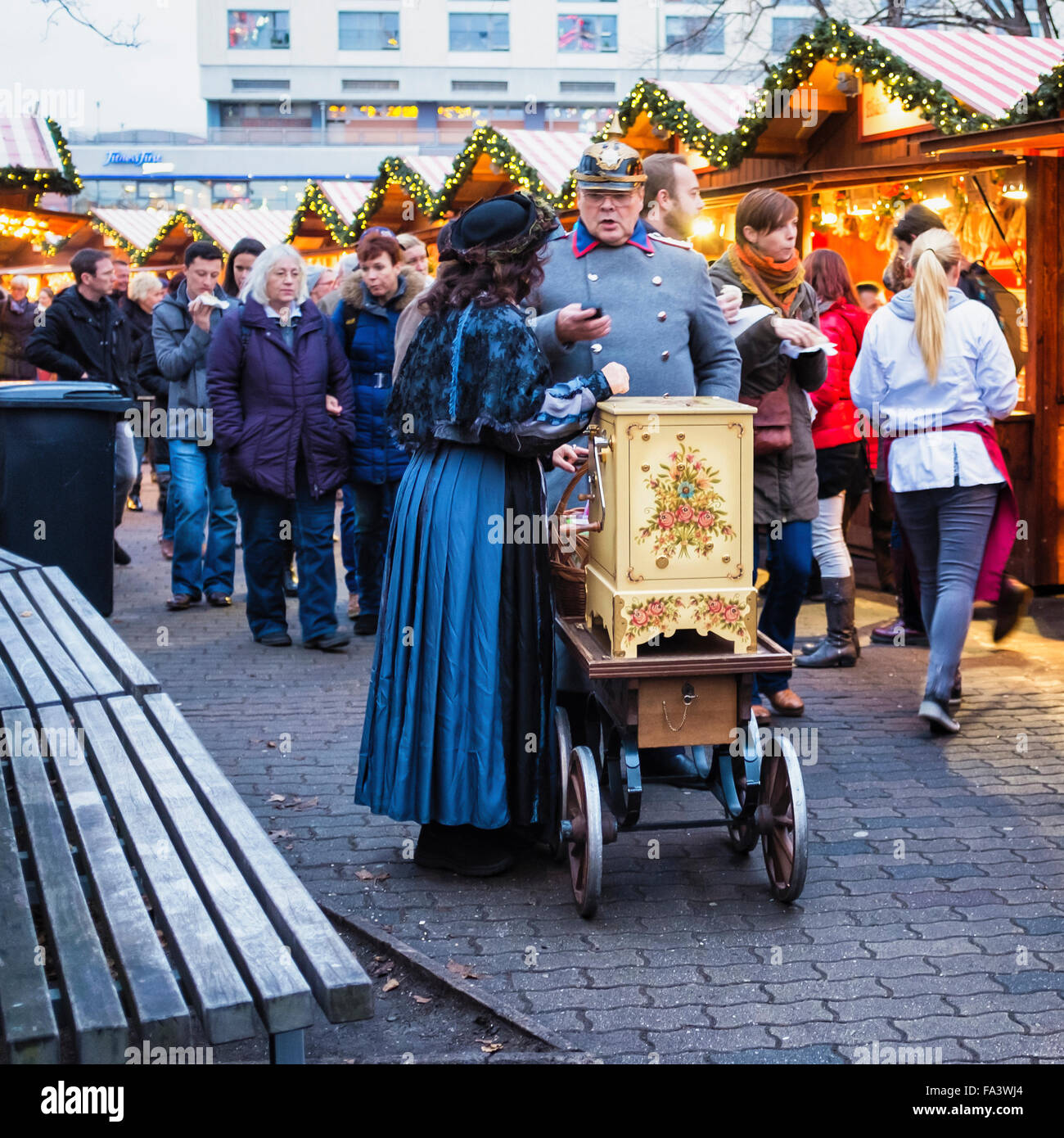Berlin, Weihnachtszeit German Christmas market with stalls and organ grinder in period dress. - Stock Image
