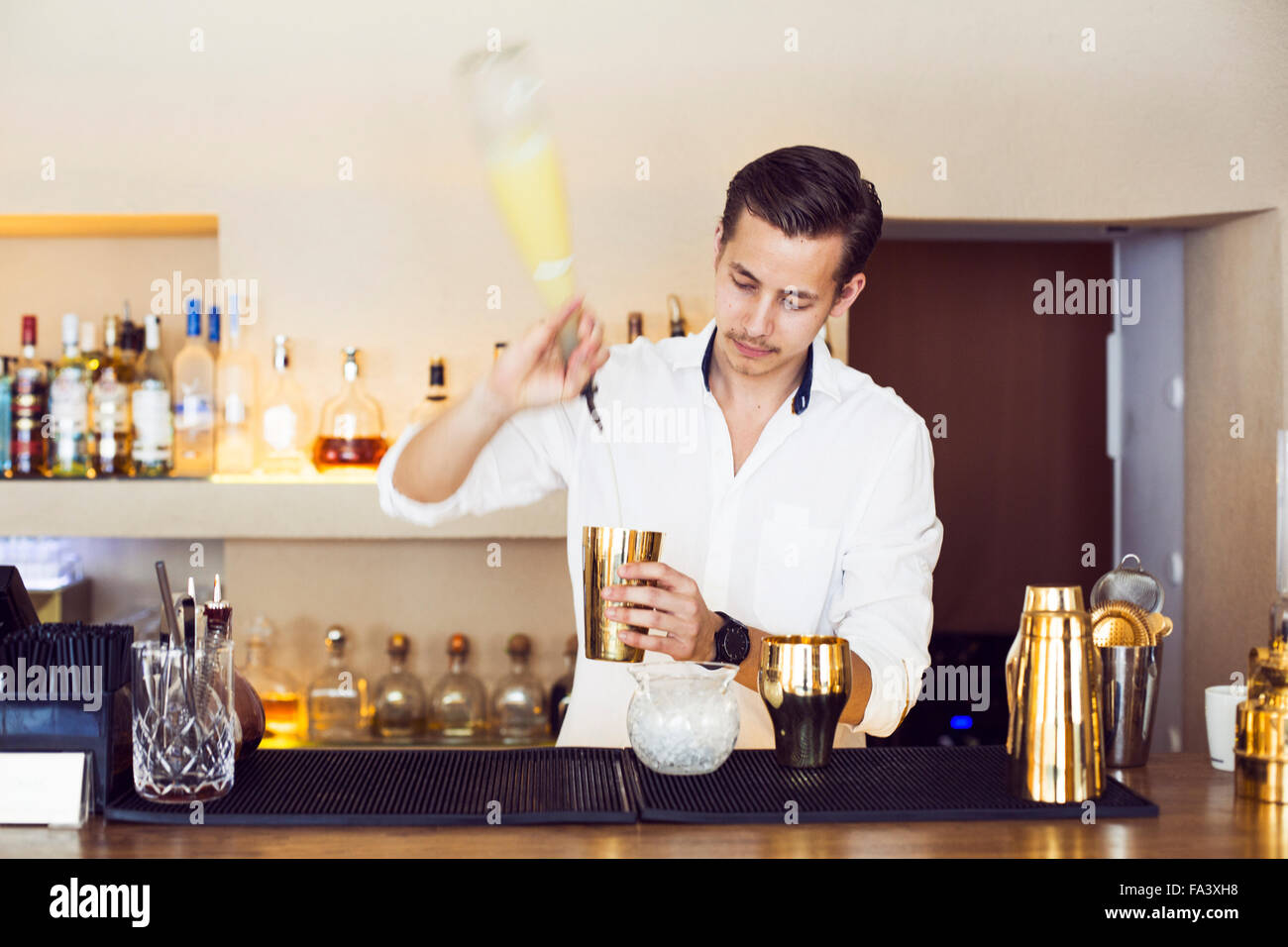 Male bartender making drink at counter in Lebanese restaurant - Stock Image
