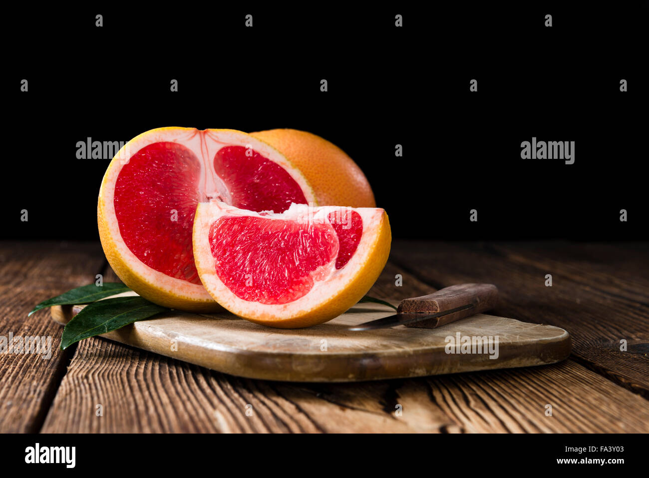 Portion of fresh Grapefruit on an old wooden table (close-up shot) - Stock Image