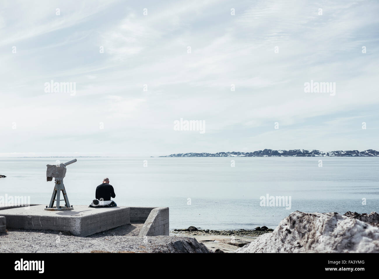 Rear view of man sitting by telescope overlooking sea against sky - Stock Image