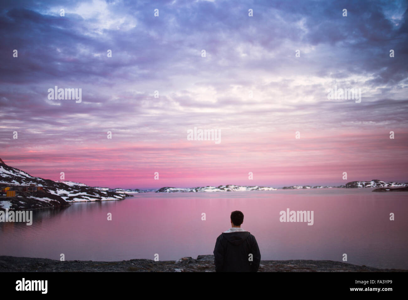 Rear view of young man on shore enjoying the sunset view during winter - Stock Image