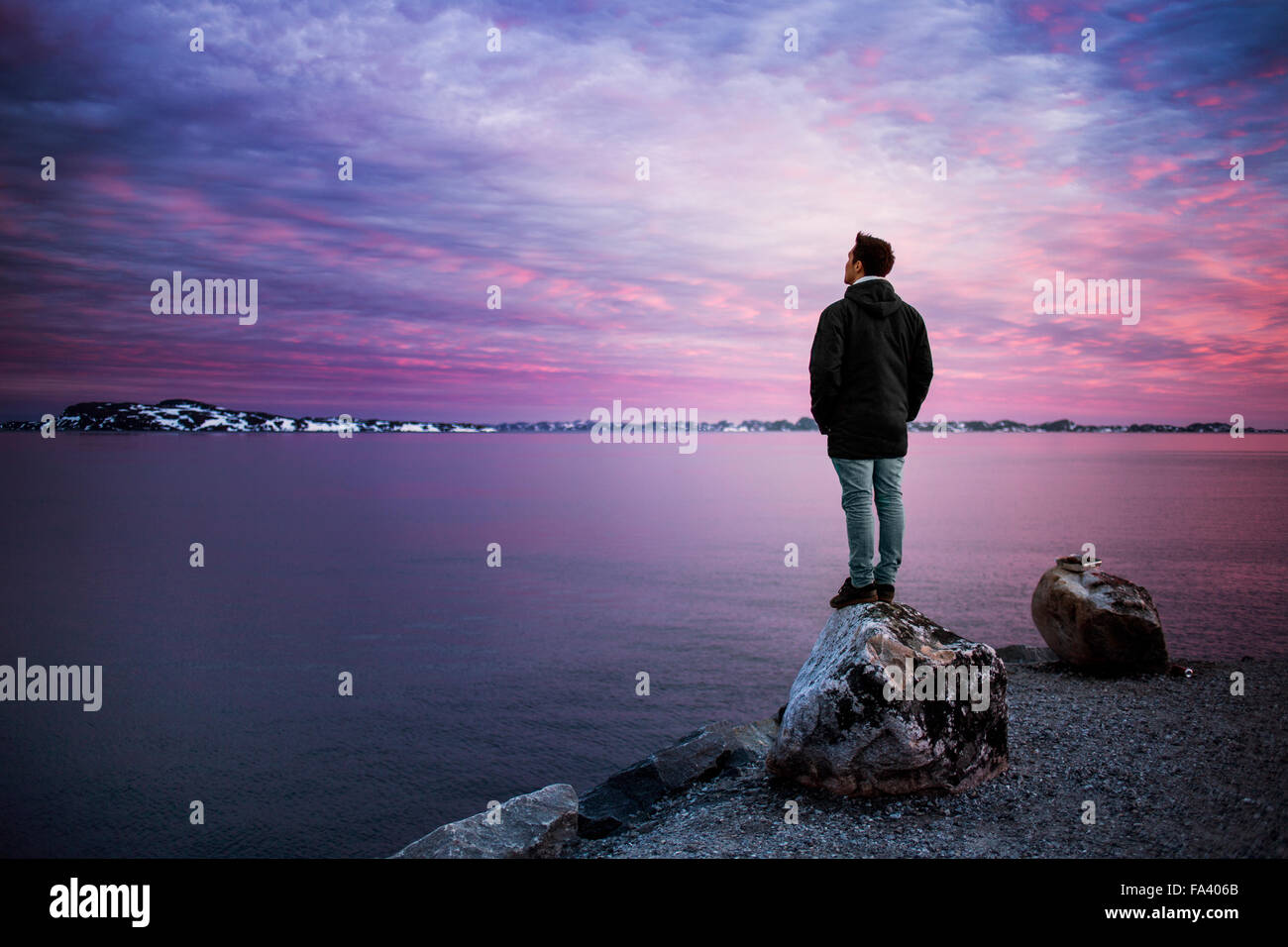 Full length rear view of man standing on rock overlooking sea during sunset - Stock Image