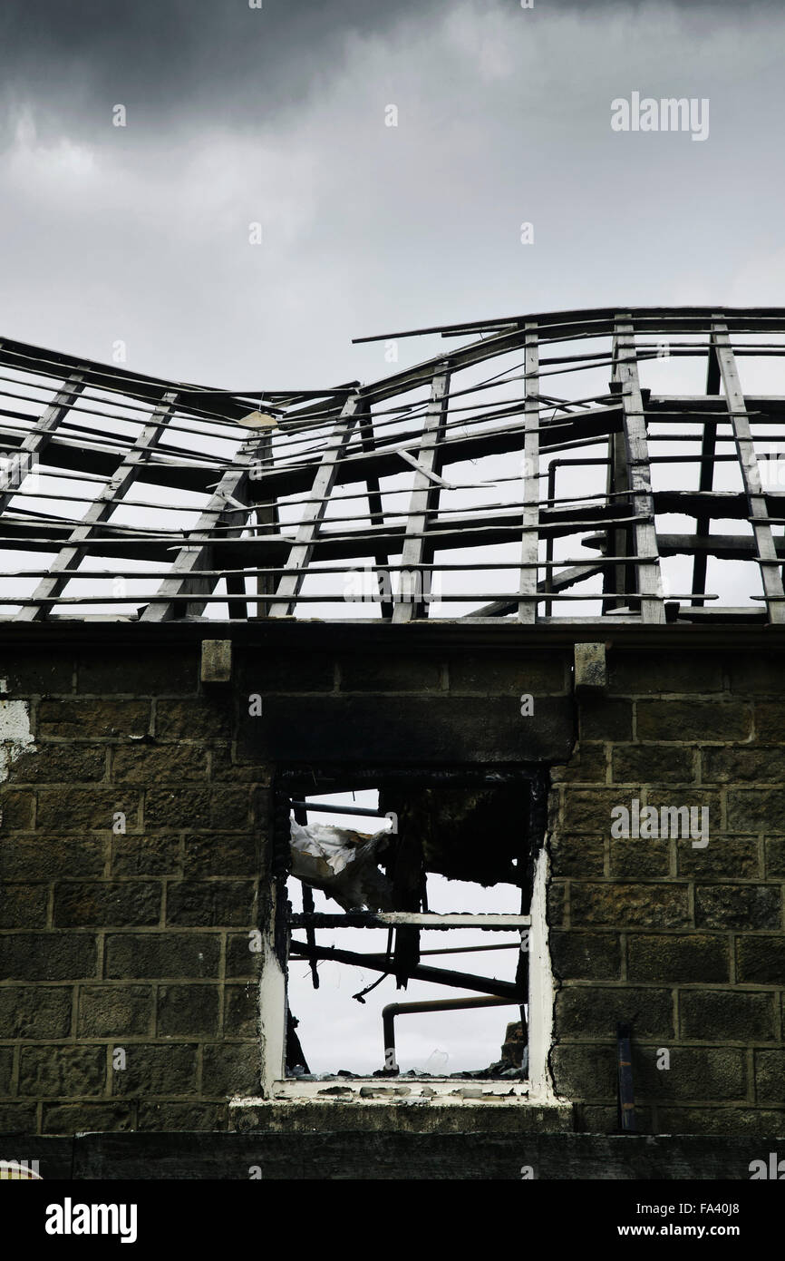 Burnt out roof and upper window of a stone building in the aftermath of a fire. Building now demolished & no - Stock Image