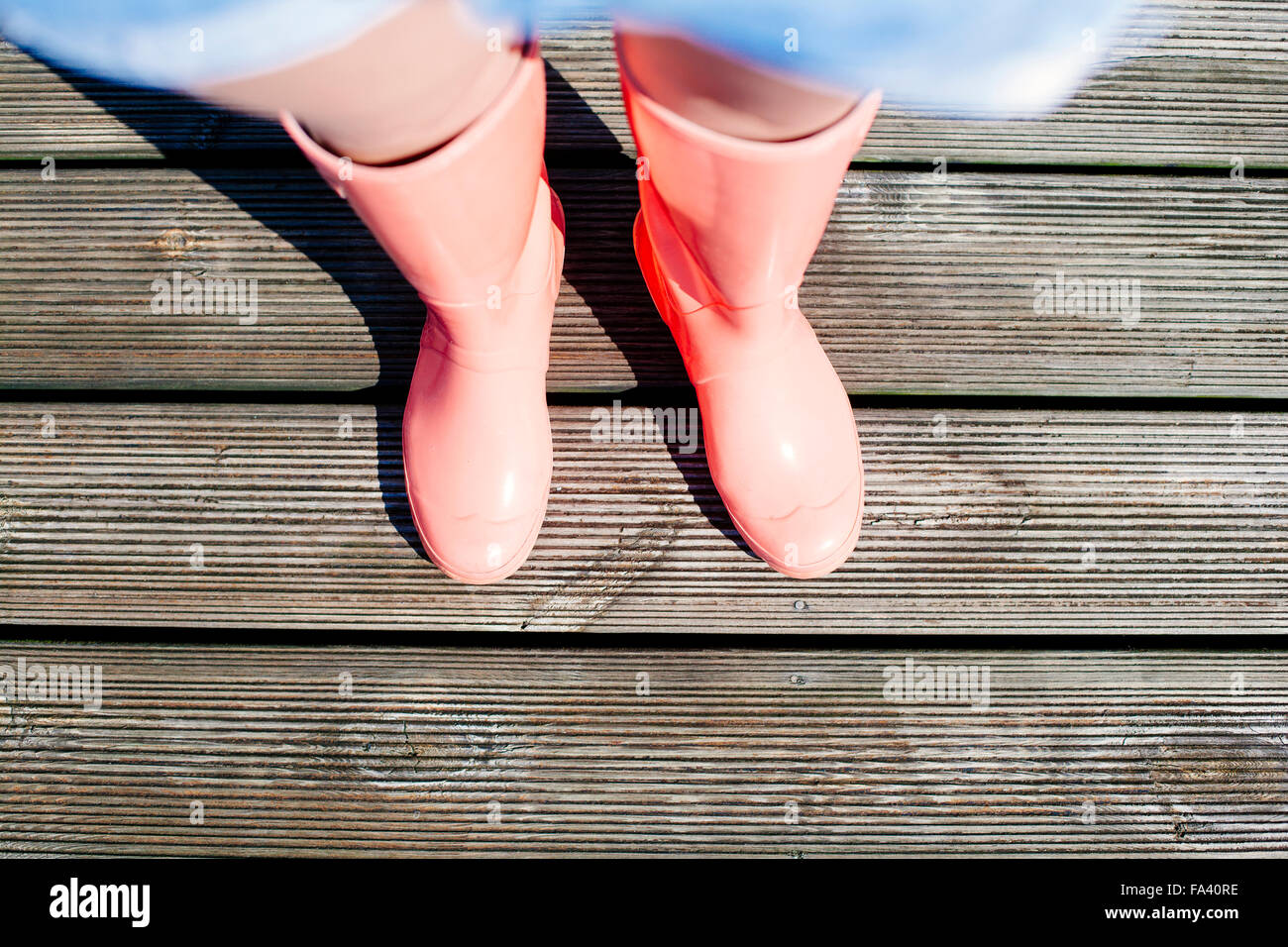 Low section of young woman standing on wooden pier - Stock Image