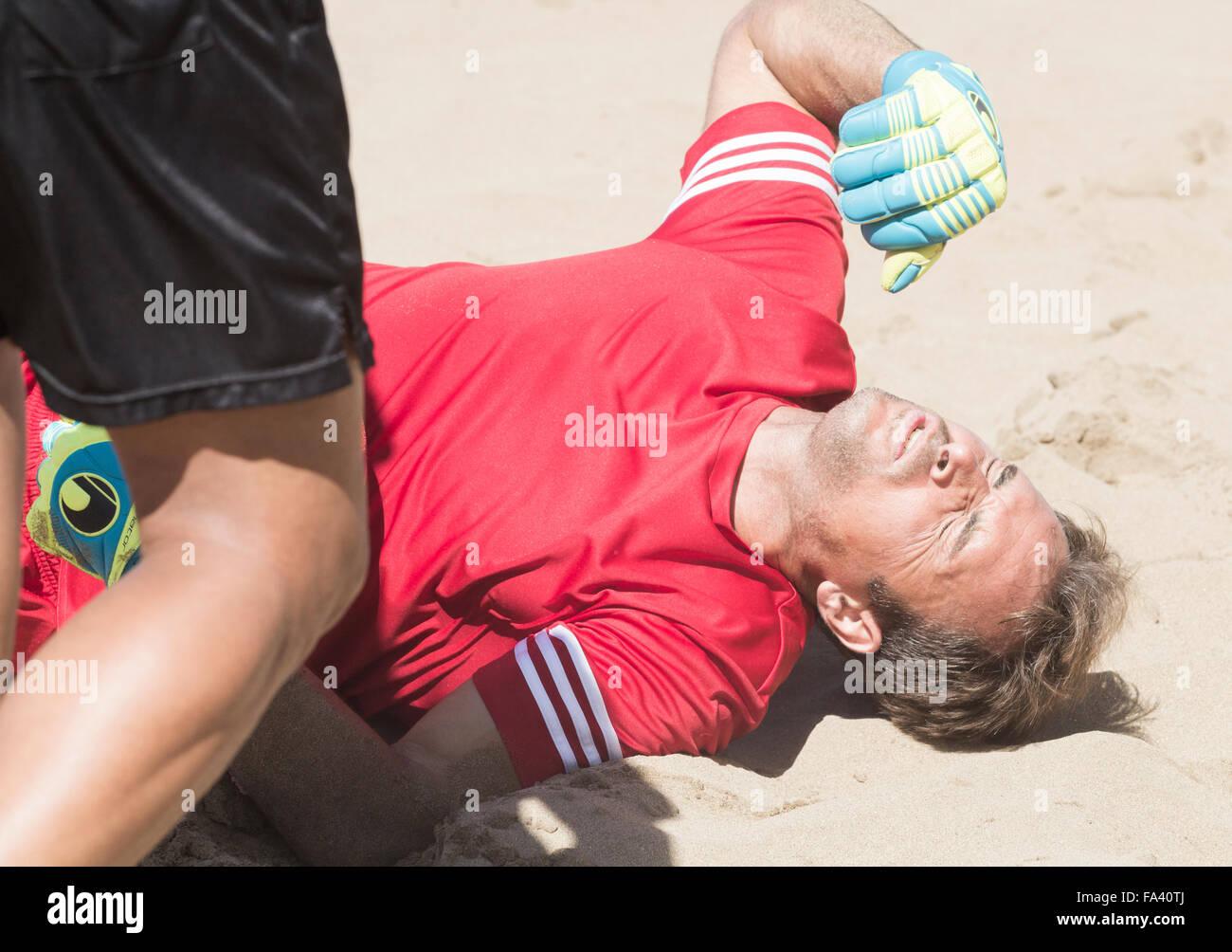 Injured goalkeeper at beach football tournament in Spain - Stock Image
