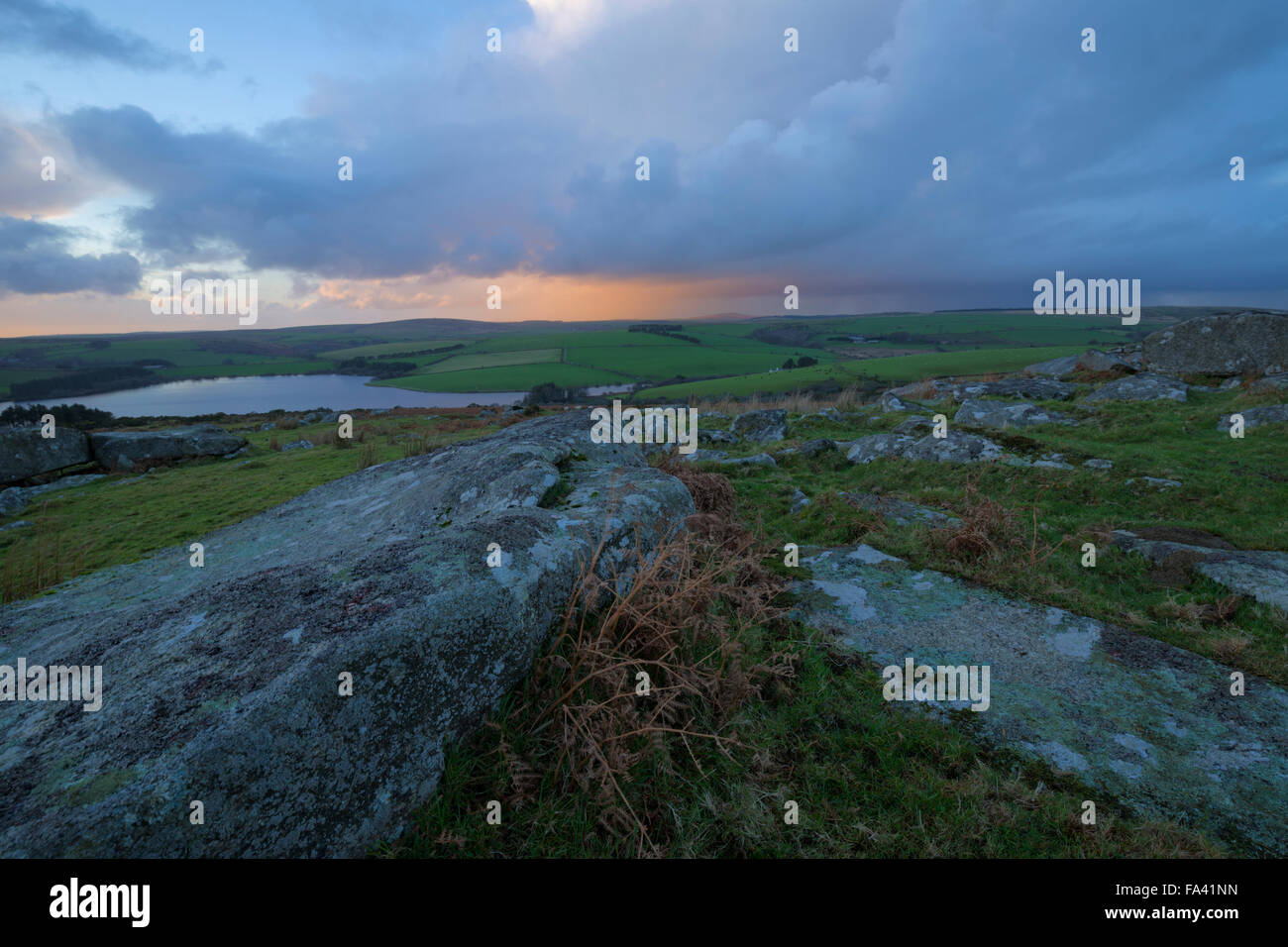 Sun setting from the top of Tregarrick tor looking across to Siblyback lake on Bodmin Moor - Stock Image