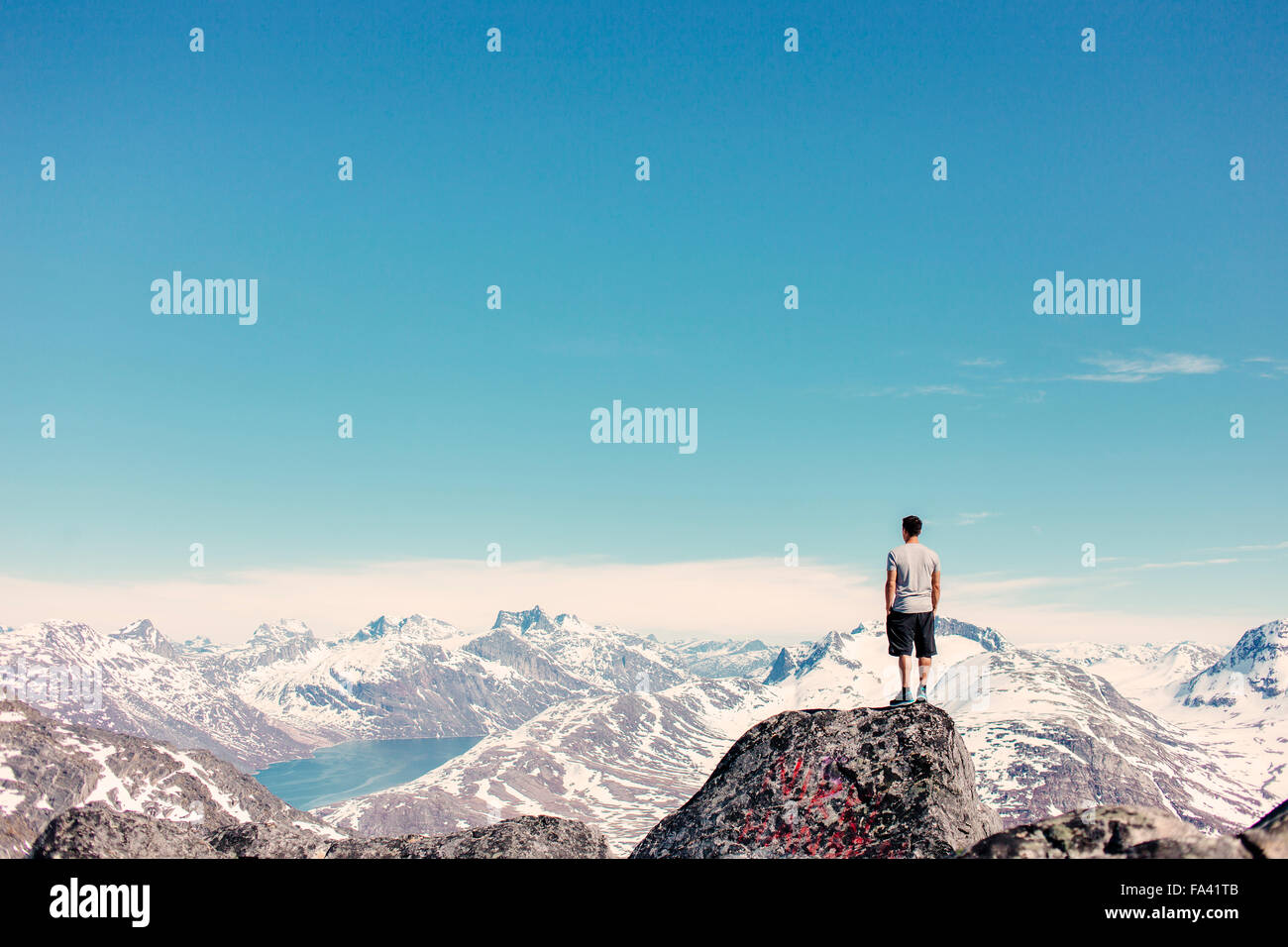 Rear view of man standing on top of rock looking at snow covered mountains - Stock Image