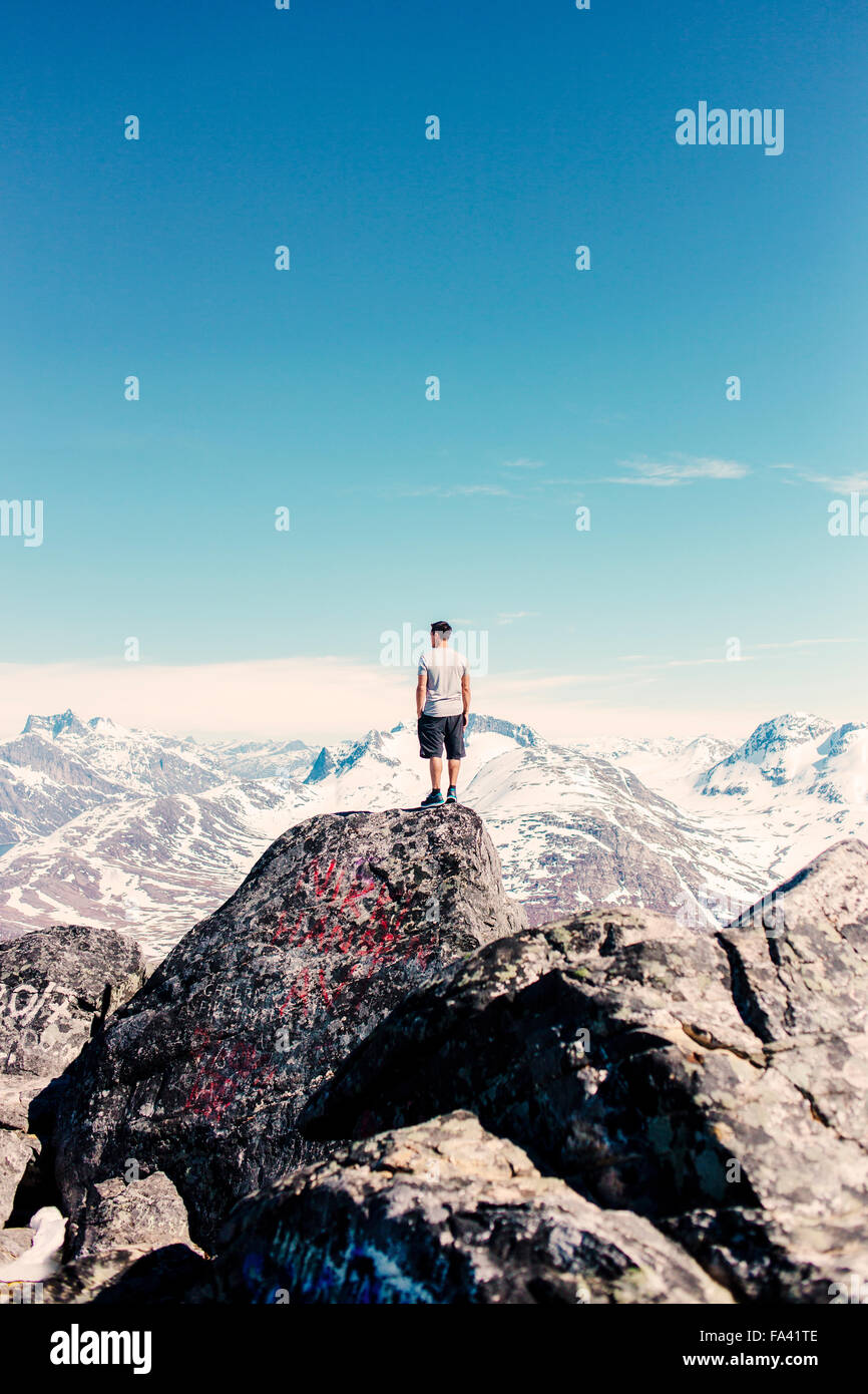 Rear view of man standing on rock looking at snow covered mountains - Stock Image