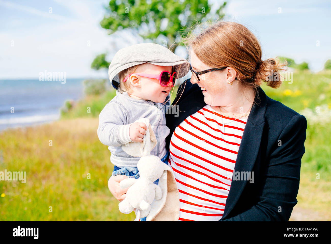 Happy mother carrying son while standing on beach Stock Photo