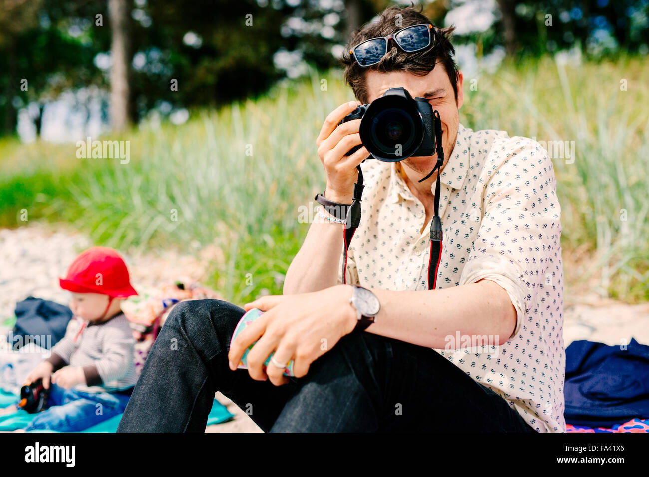 Man photographing using SLR camera - Stock Image