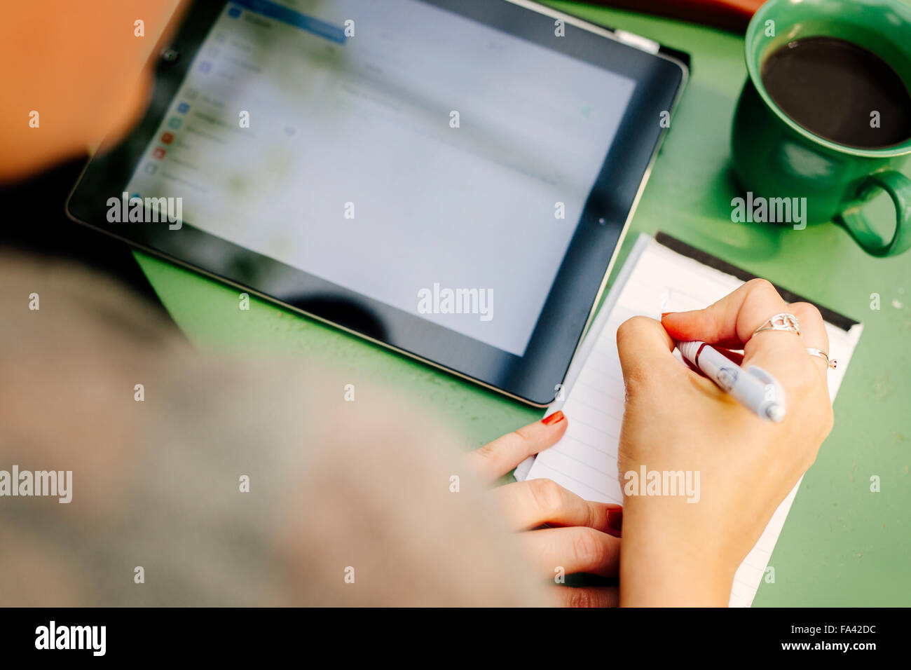 Over the shoulder view of woman with digital tablet writing on notepad - Stock Image