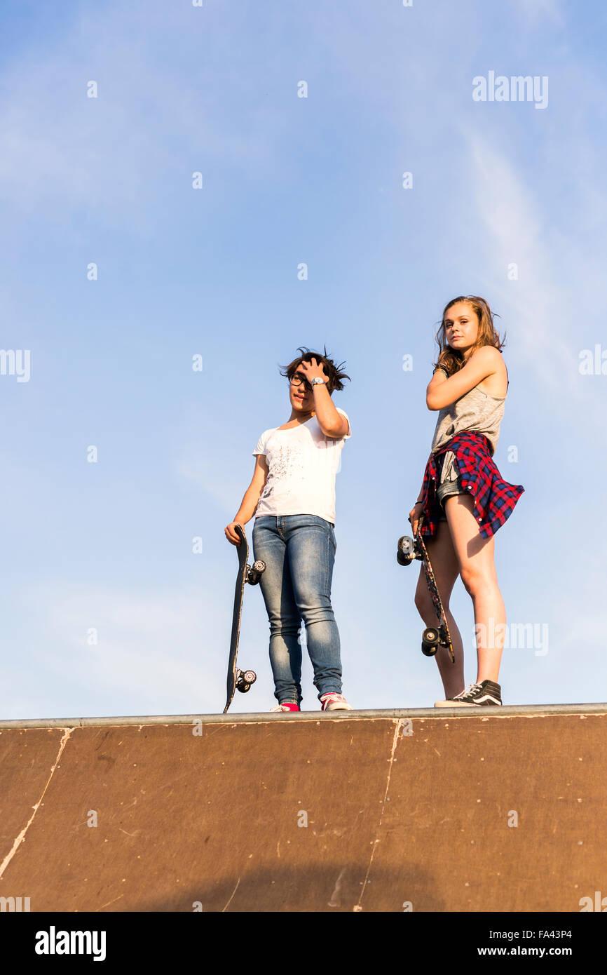 Full length of female friends with skateboards in skate park - Stock Image