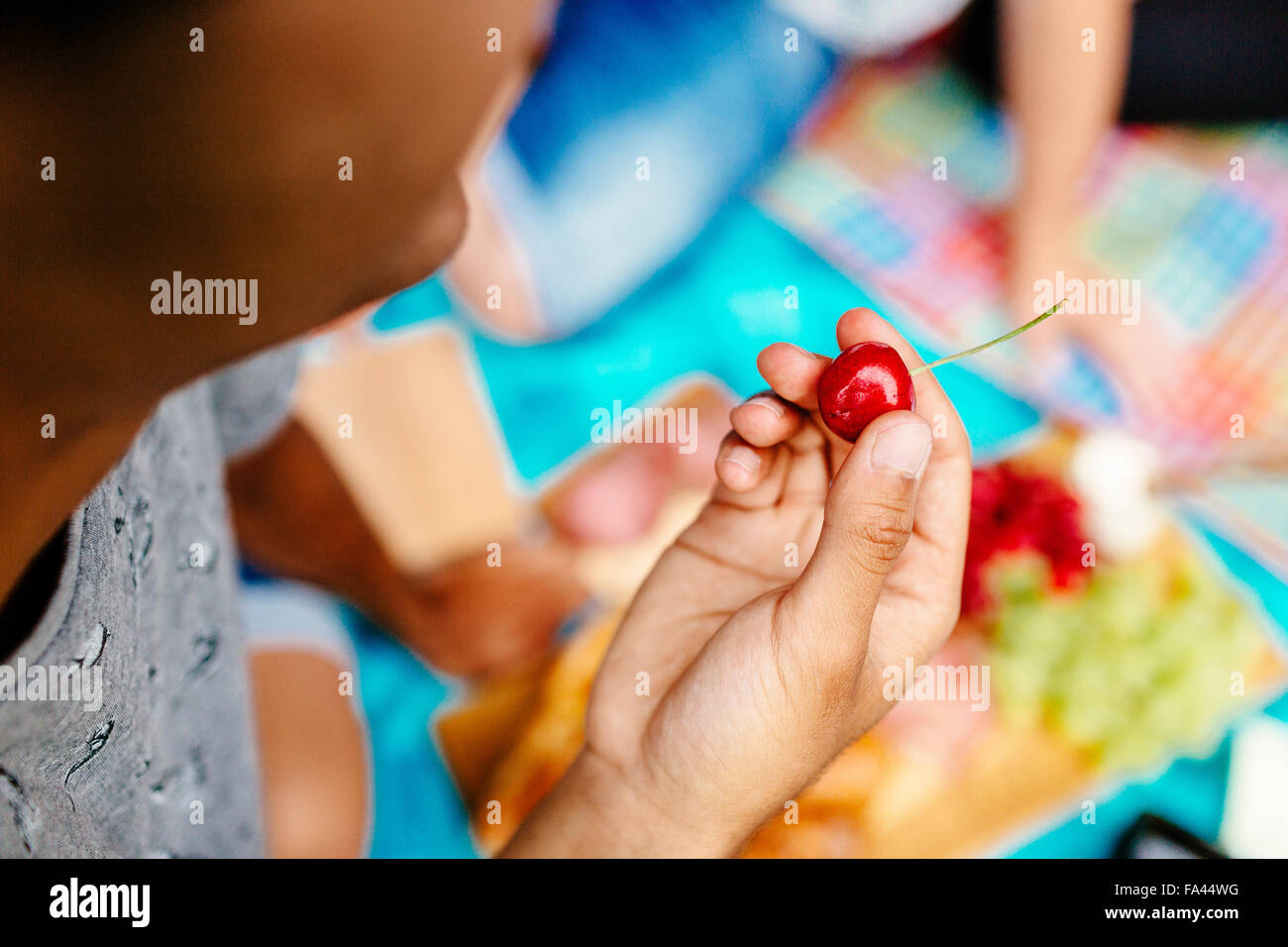 Cropped image of man holding cherry at park - Stock Image