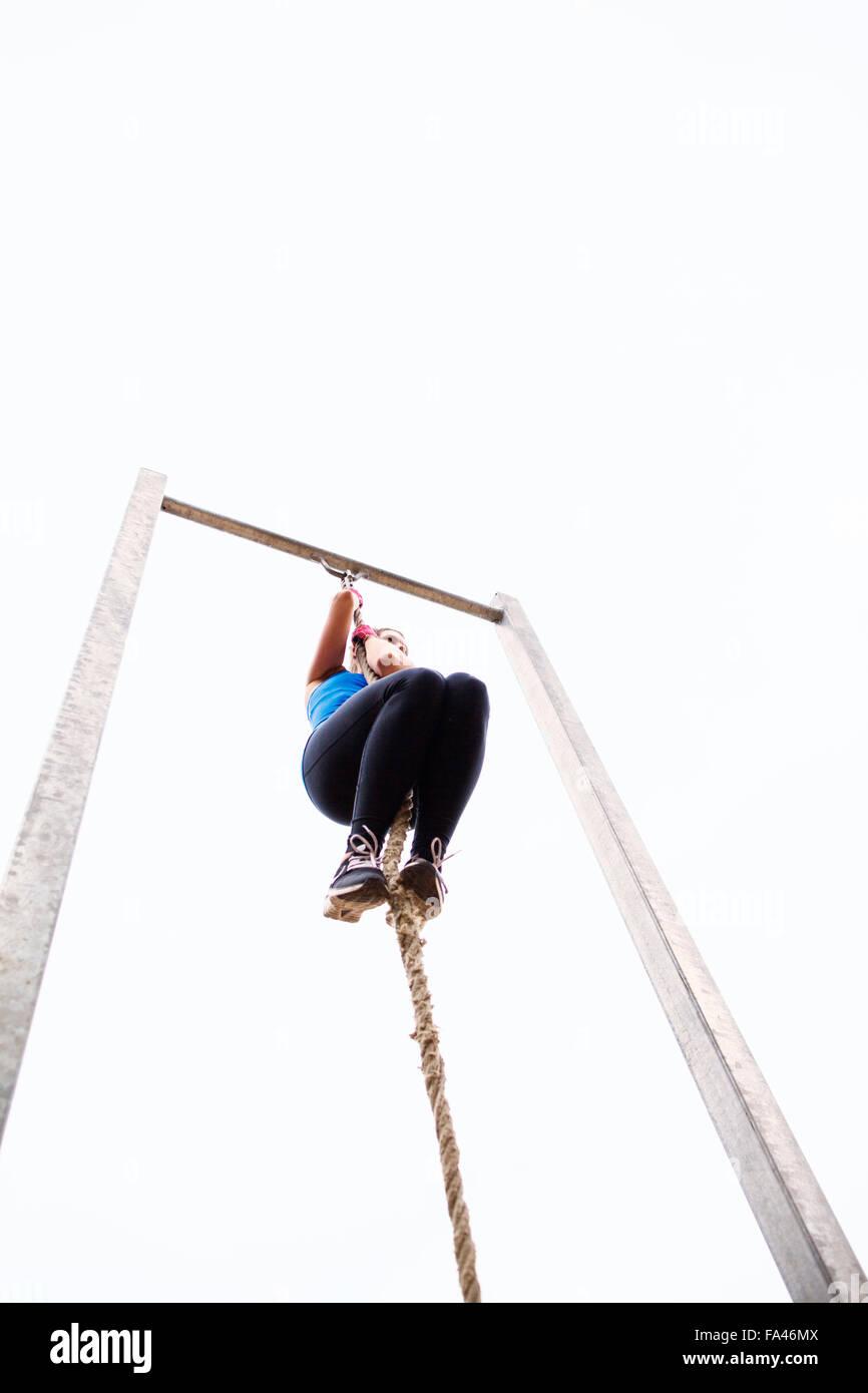 Athlete climbing rope - Stock Image