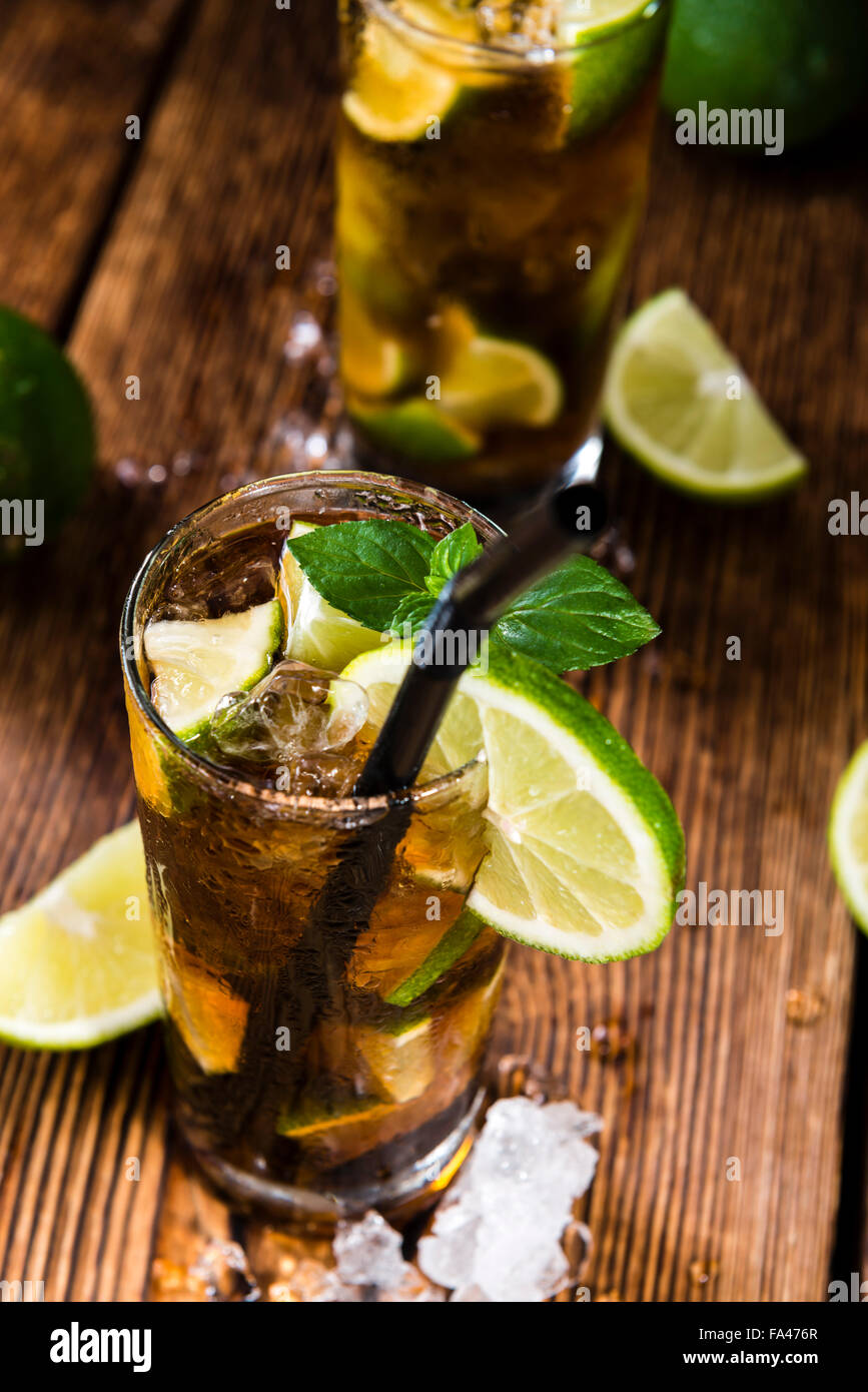 Homemade Cuba Libre with fresh lime, brown rum and crushed ice on an old wooden table - Stock Image