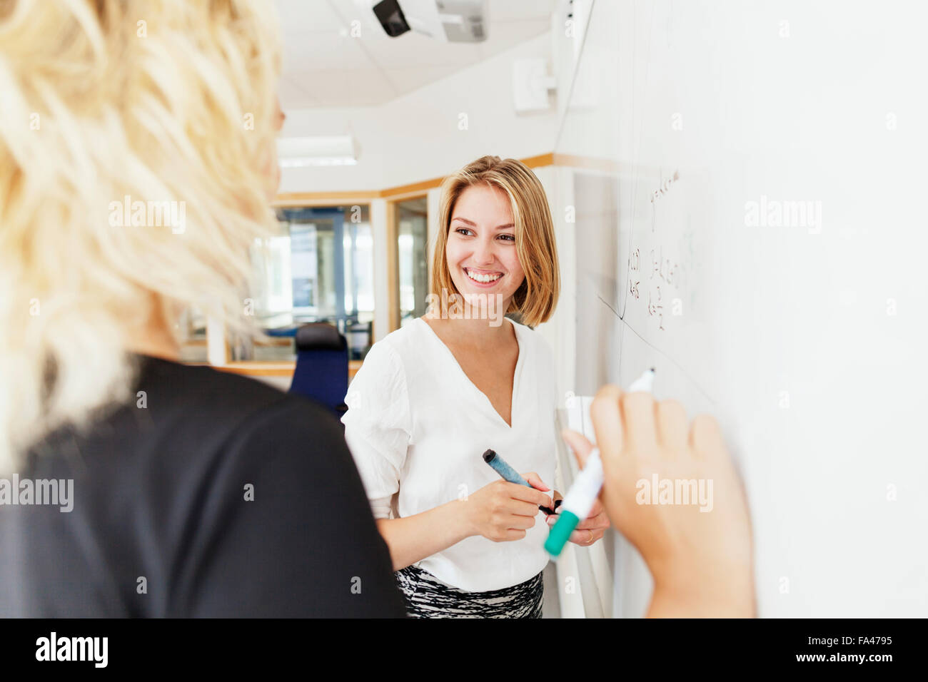 Smiling young woman with classmate standing by whiteboard in classroom - Stock Image