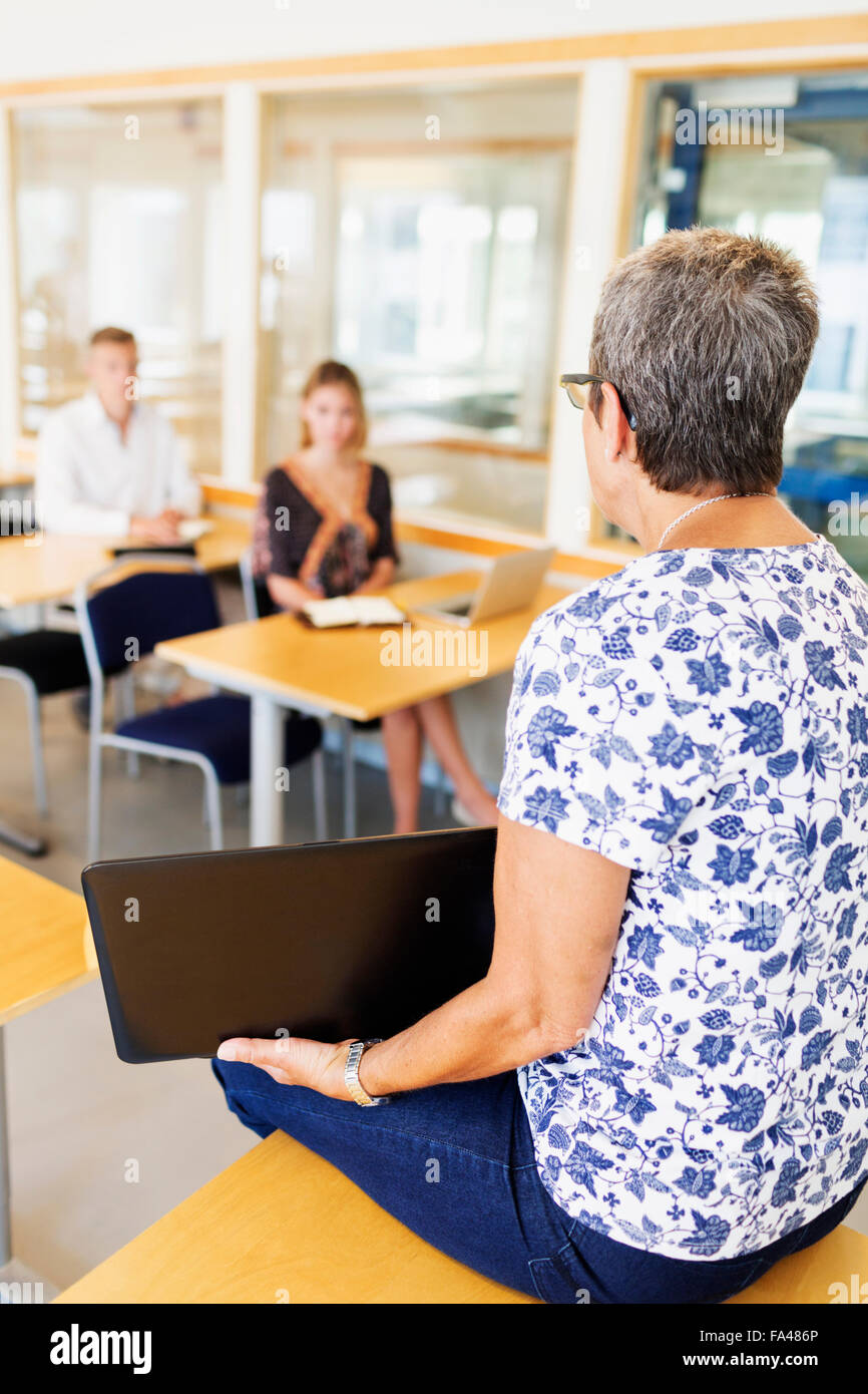 Mature female teacher holding laptop while teaching students in classroom -  Stock Image