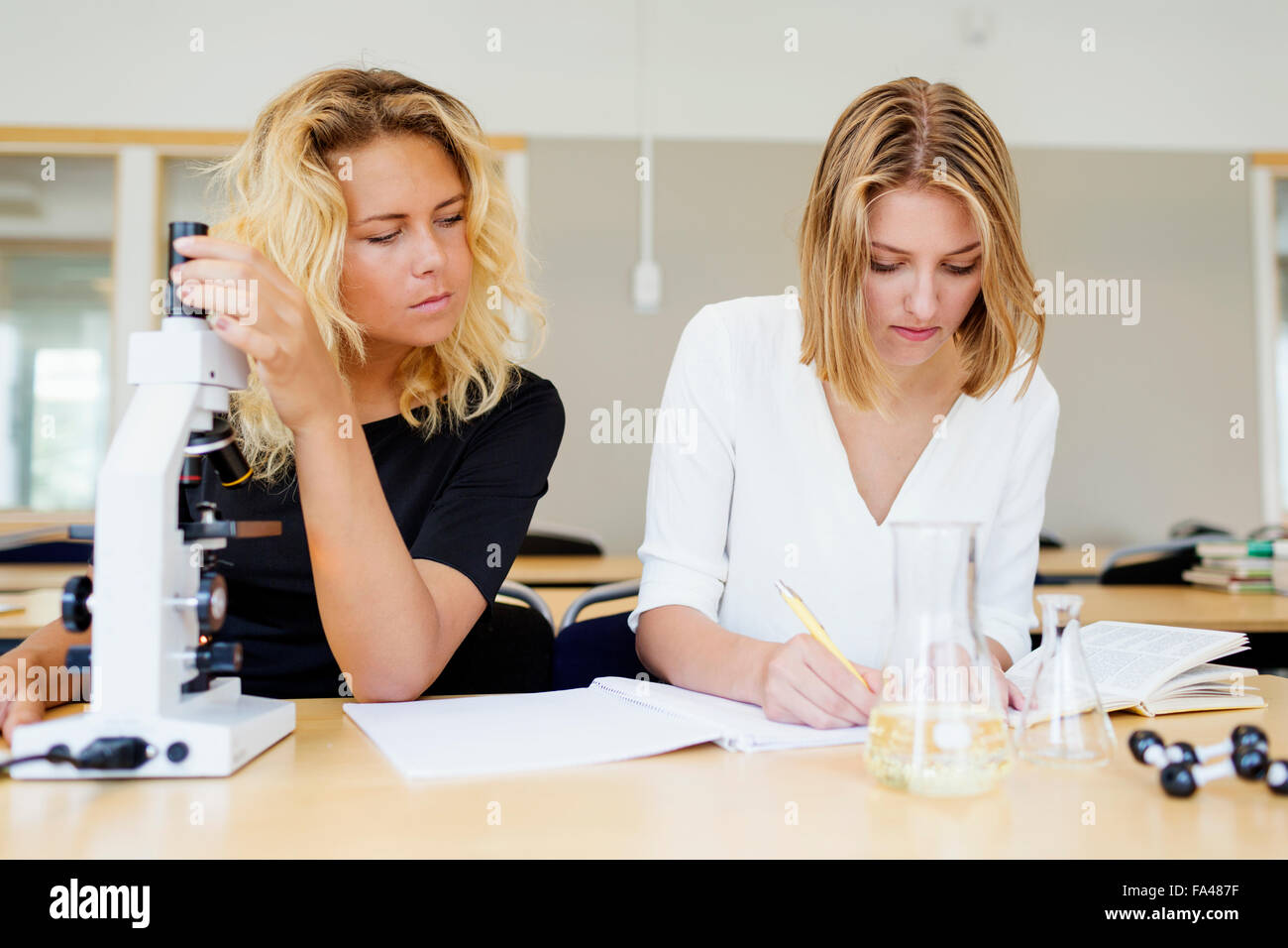 Science student using microscope while classmate writing in book at laboratory - Stock Image