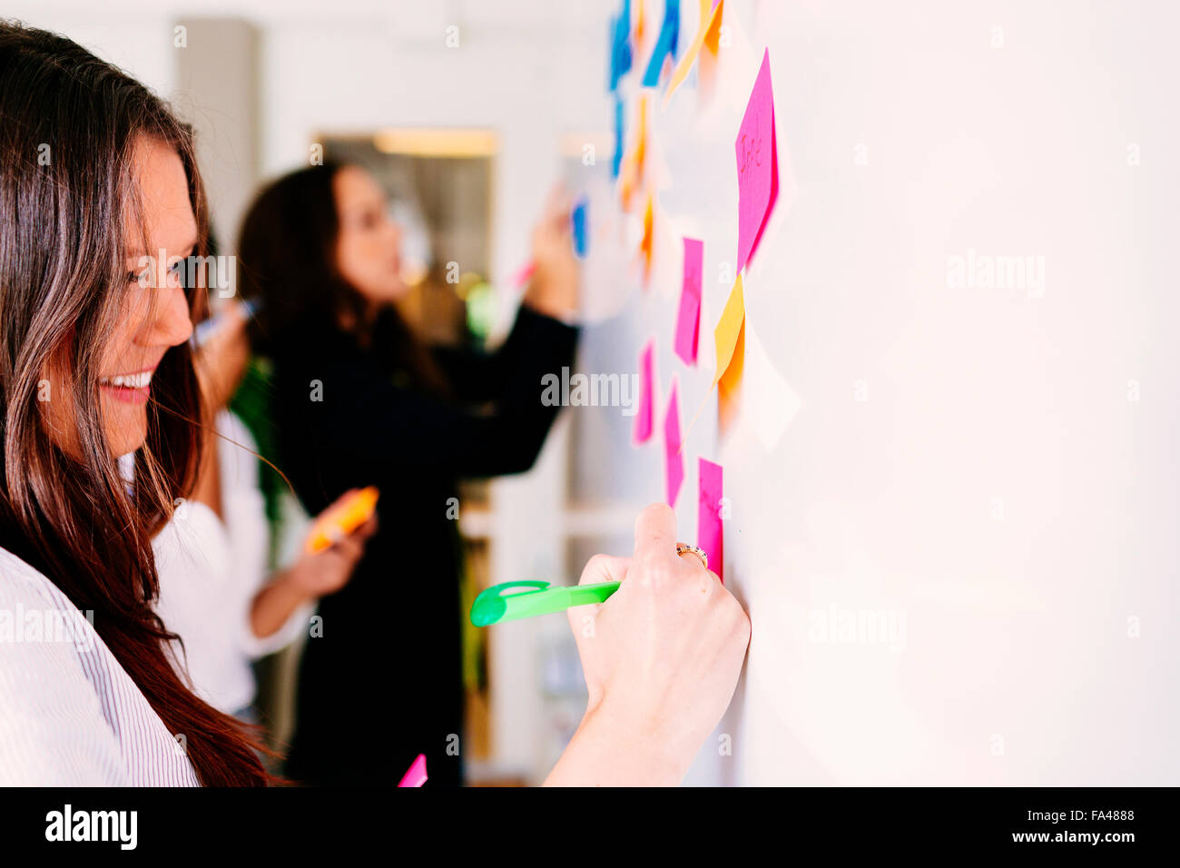 Businesswomen fixing sticky notes at office - Stock Image