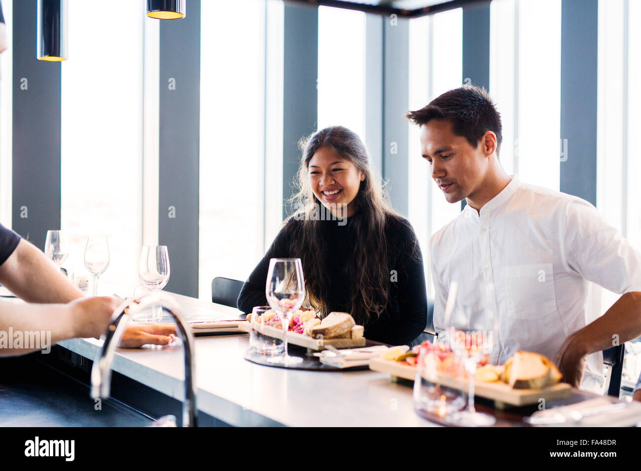 Happy friends looking at dishes in Sky bar restaurant - Stock Image