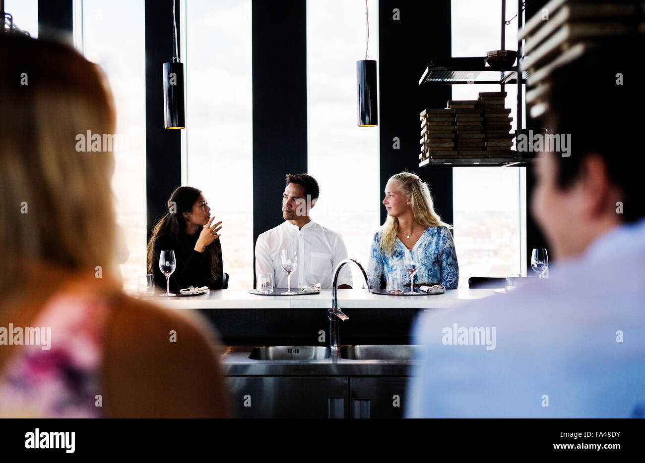 Friends communicating at table in Sky bar restaurant - Stock Image