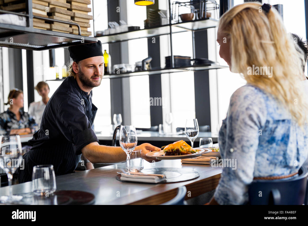 Chef serving dish to woman at Sky bar restaurant - Stock Image