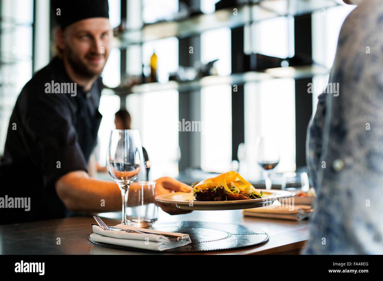Chef serving dish to customer at Sky bar restaurant - Stock Image