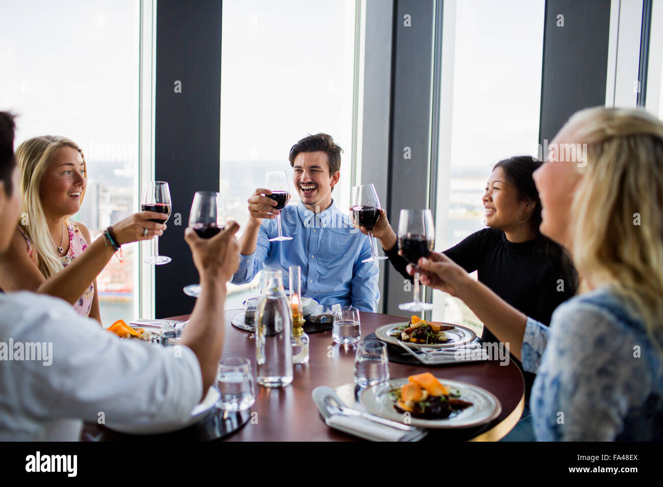 Happy friends toasting with red wine at Sky bar restaurant - Stock Image